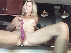 Nude blonde spreads out her gams rubbing pussy with a huge dildo
